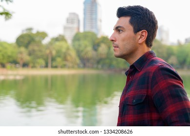 Profile view of young handsome Hispanic hipster man at the park