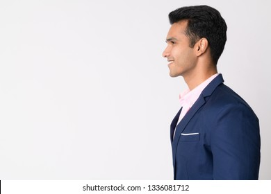 Profile view of young happy Indian businessman in suit smiling