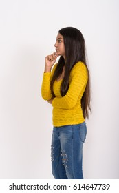 Profile view of young Indian woman standing while  thinking against white background