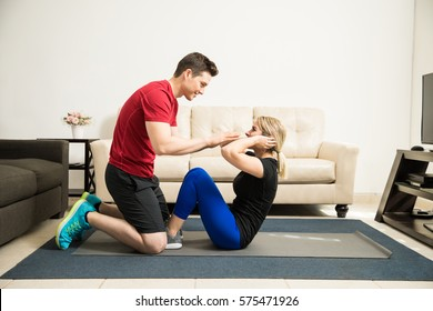 Profile view of a young Latin couple doing some crunches together and helping each other out