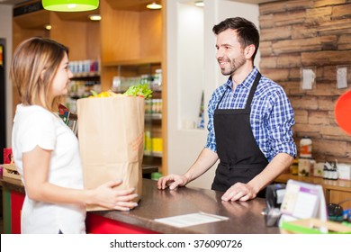 Profile view of a young male cashier helping a customer pay for all her groceries at a store