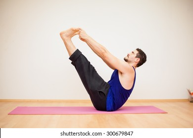Profile view of a young man doing the boat pose during yoga practice at a gym
