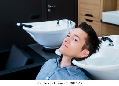 Profile view of a young man getting ready for his hair washed