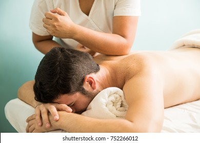 Profile view of a young man getting a lomi lomi massage in a spa clinic
