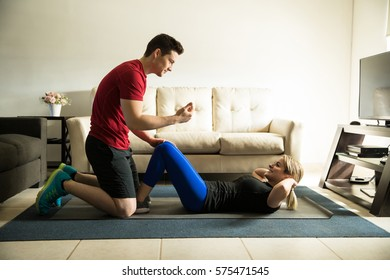 Profile view of a young man helping his girlfriend do some crunches and exercise at home