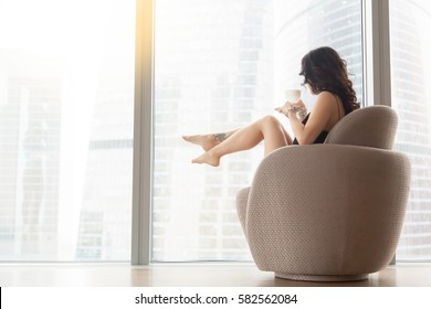 Profile view of a young model sitting in the comfortable round modern armchair indoors, wearing nightwear, holding a cup, looking at the city after waking up, relaxing after busy day, enjoying coffee