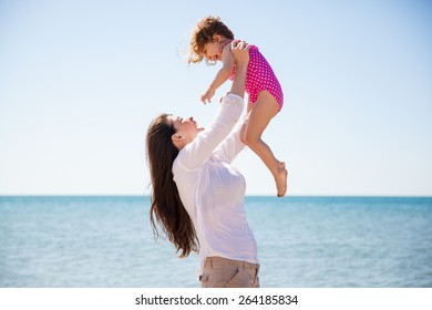 Profile view of a young mother having some fun at the beach and lifting her little girl up in the air