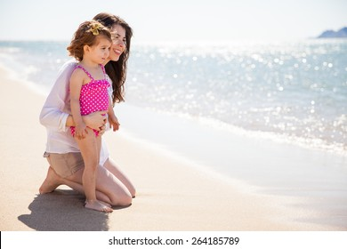 Profile view of a young single mother spending a day at the beach with her daughter