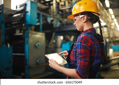Profile view of young technician in checked shirt inspecting industrial machine and taking necessary notes on digital tablet