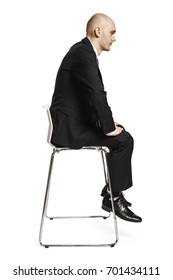 Profile view of young tired office worker sitting on a chair. Studio shot isolated on white background.