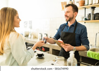 Profile view of a young woman paying for her coffee with a credit card in a coffee shop