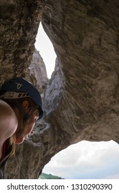 Profile of a woman climber, from the side, wearing a blue helmet, just beneath a rock cave called Hilli's Cave, in Turda Gorge (Cheile Turzii) Romania.