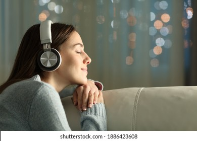 Profile of a woman with closed eyes feeling and listening to music with wireless headphones sitting on a couch in the night at home