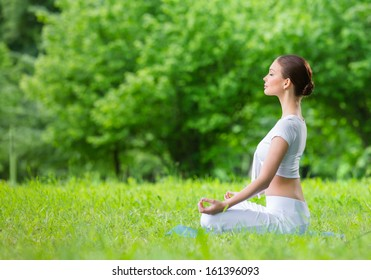 Profile of woman with eyes closed who sits in asana position zen gesturing. Concept of healthy lifestyle and relaxation