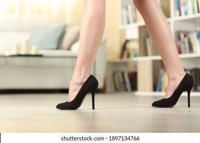 Profile of woman legs with high heels walking in the living room at home