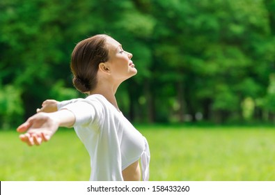 Profile of woman with outstretched arms and eyes closed. Concept of healthy lifestyle and relaxation