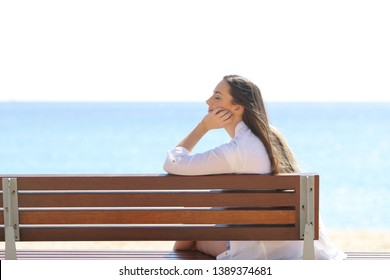 Profile of a woman relaxing sitting on a bench on the beach on summer