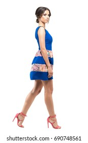 Profile of woman in short summer sleeveless dress walking and looking at camera. Full body length portrait isolated on white studio background.