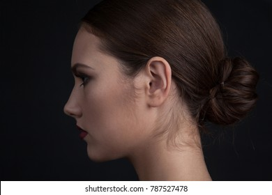 Profile of a woman's face with makeup on a black background.