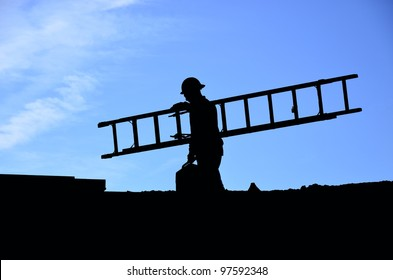 Profile of workman carrying ladder on construction project with blue sky background