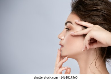 profile of young and beautiful woman touching face with light make-up, progiled girl shot with perfect nose