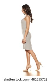 profile of a young beautiful woman walking in a short dress and high heels