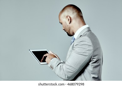 Profile of a young businessman working on a tablet isolated over grey
