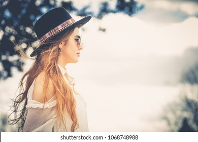 Profile of a young fashionable woman with light brown long hair and with hat and sunglasses. Looking forward outdoors. Intense sun and light.