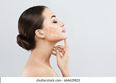 Profile of young female with clean fresh skin, antiaging concept. Girl touching face with closed eyes, lifting arrows showing facial anti-aging treatment on skin