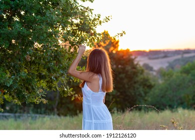 Profile of a young girl dressed in white with her head turned towards the setting sun while touching the magic tree
