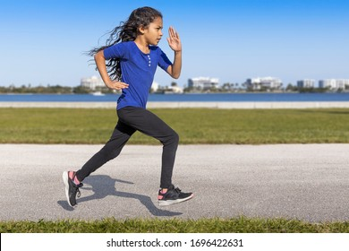 A profile young girl focused driven running with a sharp, intense body language at the waterfront park. She is staying on track while training for a competitive sport is essential to winning.