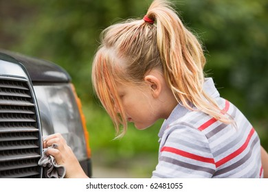 Profile of young girl washing car
