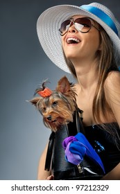 Profile of young glamor woman with Yorkshire Terrier dog in her bag