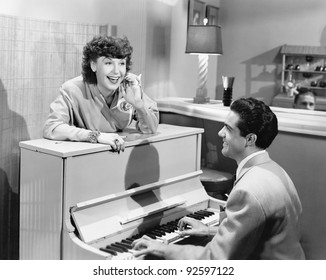 Profile of a young man playing a piano with a young woman standing in front of him and smiling and singing