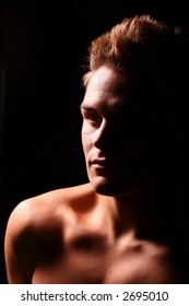 Profile of a young muscular man staring upwards in color