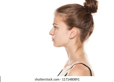 Profile of young serious woman on white background