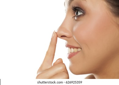 Profile of young smiling woman touching her nose