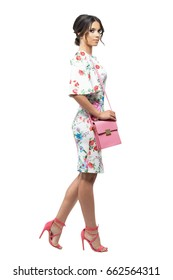 Profile of young stylish woman in dress with pink bag walking looking at camera. Full body length portrait isolated on white background.
