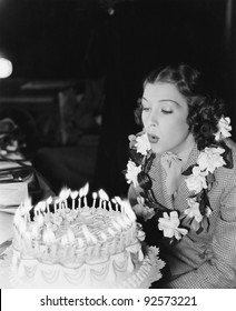 Profile of a young woman blowing off candles on a birthday cake