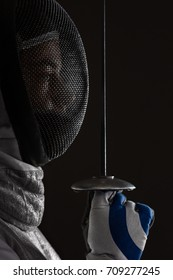 Profile of Young woman fencer wearing white fencing Mask and costume standing aside and holding the sword in front of her. Black Background
