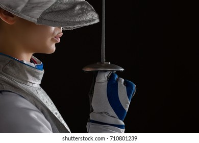 Profile of Young woman fencer wearing mask and white fencing costume and holding the sword in front of her. Dark Background