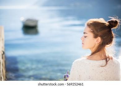 A profile of young woman. Sea and boat background