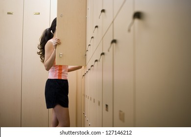 Profile of a young woman standing behind a closet door
