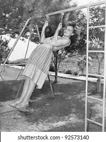 Profile of a young woman swinging on a swing in a garden