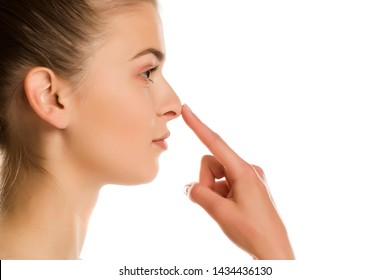 profile of young woman touches her nose on white background
