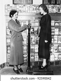 Profile of a young woman in an uniform measuring weight of another young woman on a weighing scale