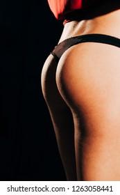 Profile of a young woman's sexy butt in black bikini.