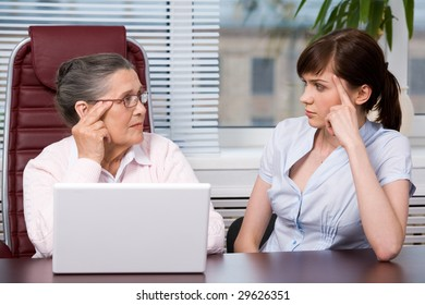 Profiles of aged woman and young female looking at each other seriously with laptop on the table