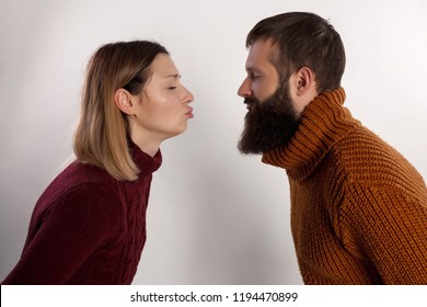 Profiles of girlfriend and boyfriend giving each other an air kiss with pout lips. Other dressed in warm knitted sweaters over gray background