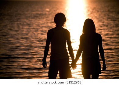Profiles of romantic couple holding each other by hands and admiring lake at sunset